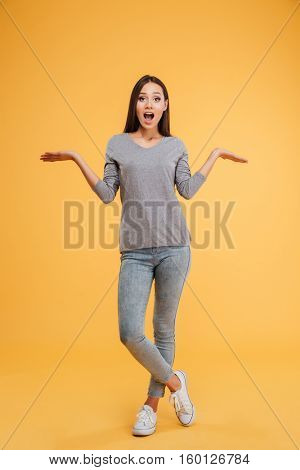 Full length surprised model in studio. Holding invisible copyspace on the pounds. isolated orange background