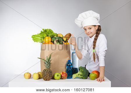 Little Girl In A Cap Cook A Variety Of Fresh Food. Girl With A Variety Of Fresh Vegetables And Fruit