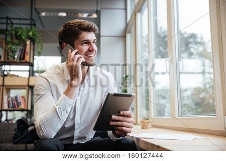 Smiling businessman dressed in white shirt sitting in cafe and using tablet computer while talking by his phone. Look aside.