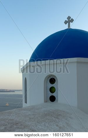 Church with blue roof in town of Oia and panorama to Santorini island, Thira, Cyclades, Greece