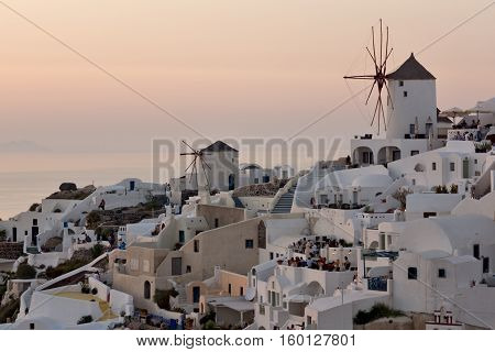 Amazing Sunset over white windmills in  town of Oia and panorama to Santorini island, Thira, Cyclades, Greece