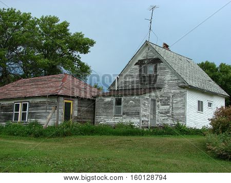 Old abandoned farm house with TV antenna still on the roof.