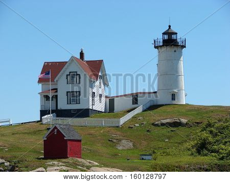 A lighthouse with living quarters alone shore line in  the East Coast USA.