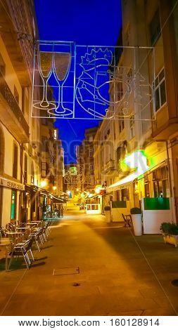 La Coruna, Galicia, Spain - November 30, 2016: Night cityscape of La Coruna, Galicia, Spain. Illuminated street in the historic center of Coruna at blue evening hour