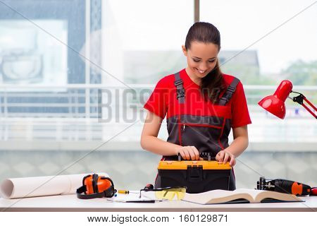 Young woman in coveralls doing repairs
