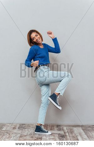 Full length young happy african woman in sweater and jeans standing sideways and rejoices. Isolated gray background