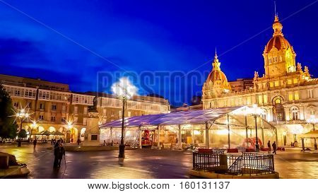 Night cityscape of Coruña, Galicia, Spain. Illuminated Municipal Palace and City Hall Square of Coruna at blue evening hour