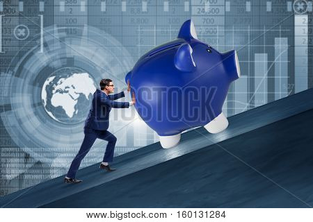 Man pushing piggybank uphill in business concept