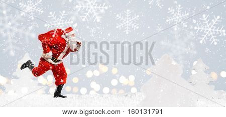 Santa Claus running at New Year or Christmas delivery rush with gift bag full of presents on snow