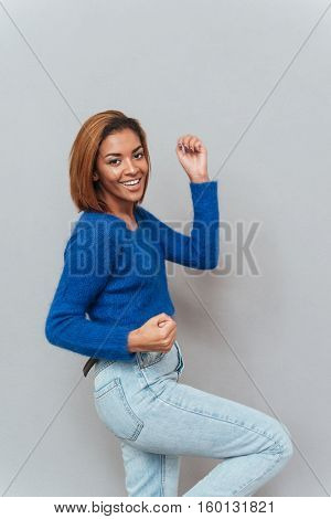 Attractive happy african woman in sweater and jeans standing sideways and rejoices. Isolated gray background