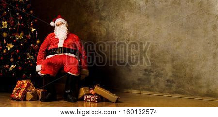 Tired Santa Claus sitting with gift boxes near decorated fir tree