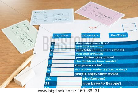 blue english verb test with cards on table
