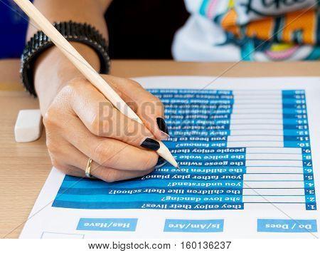 lady hand taking blue english exercise on table