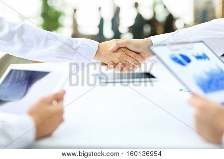 handshake business partners after the conclusion of successful contract on the background of the workplace