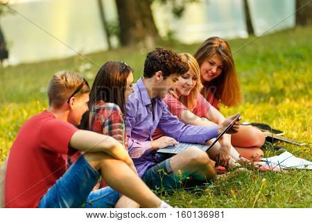 group of students with laptop in Park in spring day