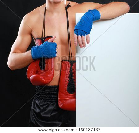 Young handsome boxer man standing near board , isolated on black background.