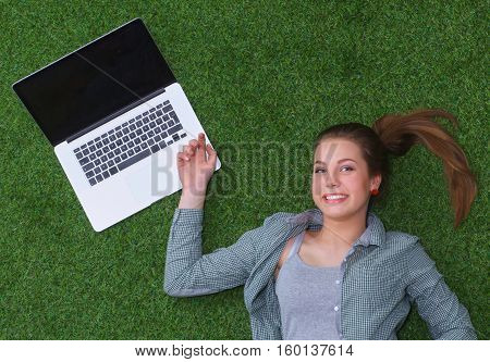 Relaxed woman  lying on the grass near laptop .