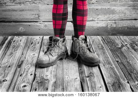 horizontal image of a pair of women's legs wearing red and black checkered leotards and standing in big old worn out work boots on a rustic wood floor.