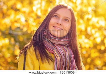 Young beautiful smiling woman in autumn park. Woman wearing fashionable colorful scarf.