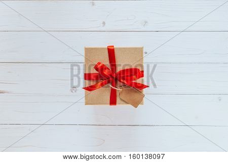 Above Brown Gift Box With Tag On Wooden Board Background. Gift Box With Red Ribbon On Wooden White B