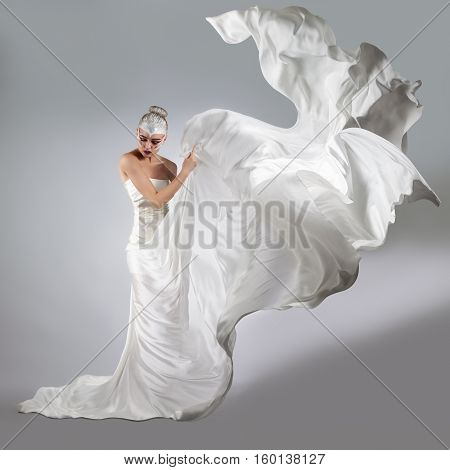 Woman With Bright Creative Make-up In A White Cloth Flying. A Girl Holding A Flying White Cloth