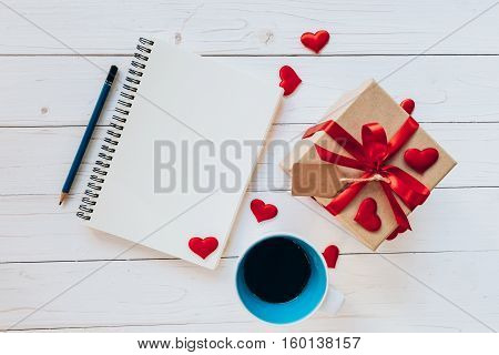Above Notebook, Coffee Cup, Gift Box, Red Ribbon, Tag And Pencil On White Wooden With Space For Text