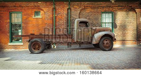 Toronto city, Ontario, Canada, May 22, 2016, beautiful amazing view of old vintage classic retro truck parked against brick building at Toronto distillery historic district area
