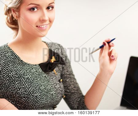 A portrait of a businesswoman sitting at a desk with a laptop.