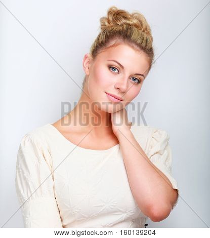 A young woman standing in white background.