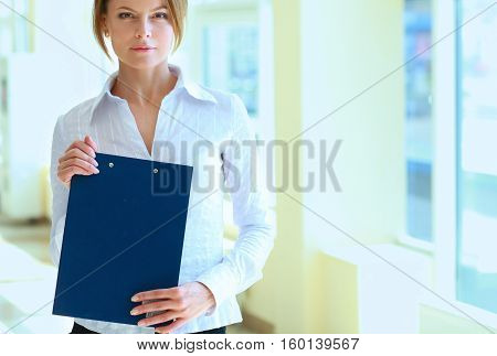 Business woman standing in foreground with a folder in her hands .