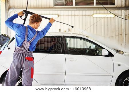 Man worker washing car on a car wash.