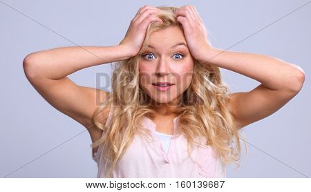 Young emotional woman, standing on grary background.