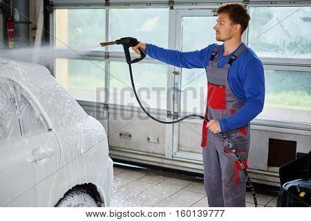 Man worker washing luxury car on a car wash.