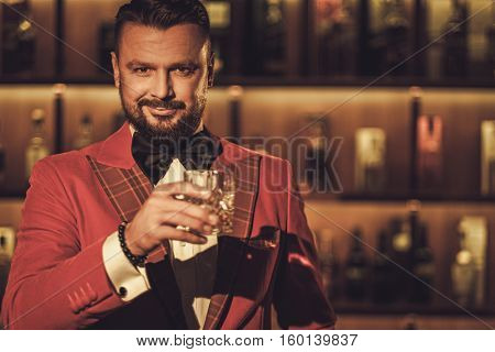 Extravagant stylish man with whisky glass in gentleman club.