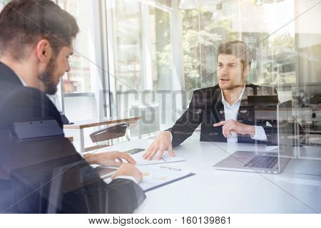 Two happy young businessmen sitting and discussing business plan on meeting in office