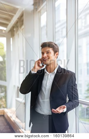 Cheerful young businessman standing and talking on cell phone in office