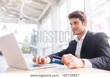 Happy young businessman using laptop and credit card at the table