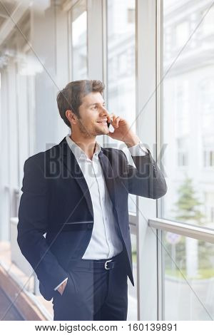 Happy young businessman talking on mobile phone near the window in office