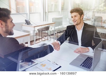 Two cheerful successful young businessmen shaking hands on business meeting in office