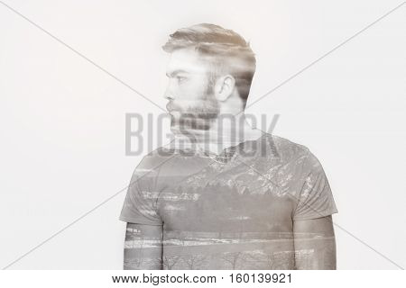 Portrait of a casual young man looking away over gray background