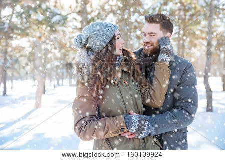 Smiling young couple looking at each other in winter park