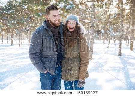 Laughing young couple standing in winter park