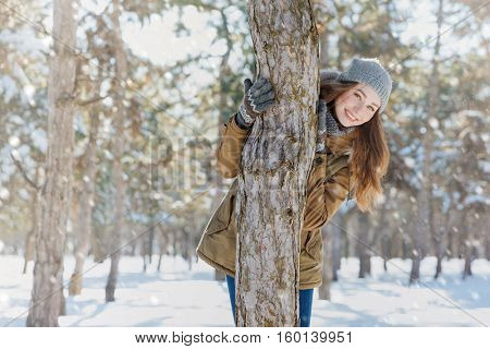 Smiling young woman walking in winter park and looking at camera