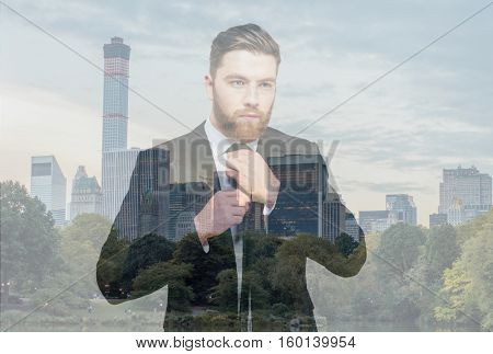 Double exposure concept of concentrated Businessman on cityscape tying a tie and looking away