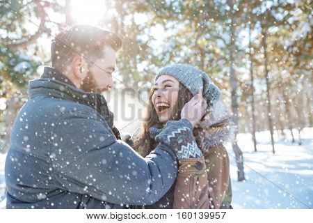 Cheerful young couple standing together in winter park