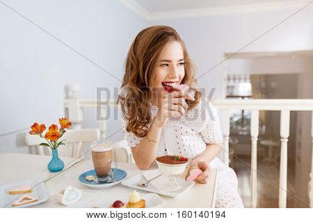 Cheerful attractive young woman with long curly hair sitting and eating heart shaped cookies