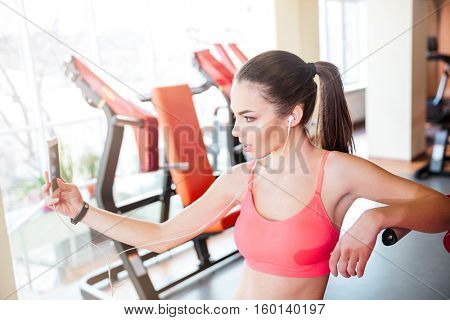 Pretty young woman athlete taking selfie and listening to music from cell phone in gym