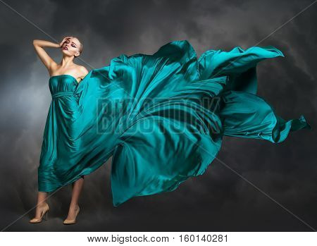 Woman In  Silk Dress Waving On Wind. Flying And Fluttering Gown Cloth Over Gray Background