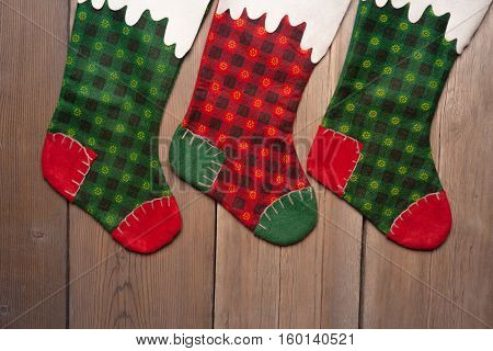 Christmas stockings hanging against wooden wall background
