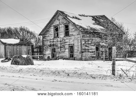 abandoned homestead on a winter day in black and white